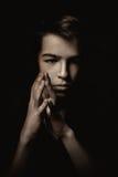 Retrato del adolescente pensativo en fondo negro Foto de archivo