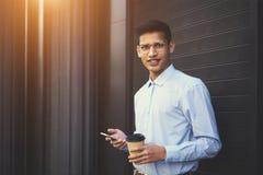 Retrato del adolescente positivo en las lentes que mandan un SMS en redes sociales Imagen de archivo libre de regalías