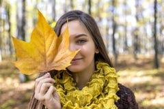 Retrato del adolescente precioso feliz que sostiene el pasto caido otoño Imágenes de archivo libres de regalías