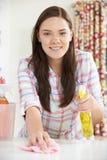Retrato del adolescente que ayuda con la limpieza en casa Foto de archivo