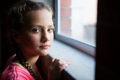 Retrato del adolescente que coloca la ventana cercana Imagen de archivo libre de regalías
