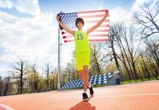 Retrato del adolescente que corre con la bandera americana Fotos de archivo libres de regalías