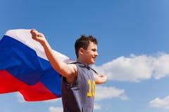 Retrato del adolescente que corre con la bandera rusa Fotos de archivo