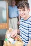 Retrato del adolescente que hace las compras para el hombre mayor Fotos de archivo libres de regalías