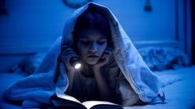 Retrato del adolescente que miente debajo de la manta y del libro de lectura Fotografía de archivo libre de regalías