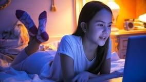 Retrato del adolescente que miente en cama en la noche con el ordenador portátil Imagen de archivo libre de regalías
