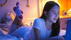 Retrato del adolescente que miente en cama en la noche y que charla en Internet Foto de archivo