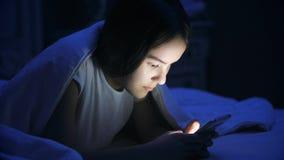 Retrato del adolescente que miente en cama en la noche y que usa el teléfono elegante Imágenes de archivo libres de regalías