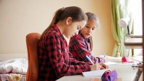 Retrato del adolescente que mira en cuaderno de su amigo Imagenes de archivo