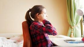 Retrato del adolescente que pone en earphonew mientras que hace la preparación Foto de archivo libre de regalías