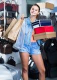 Retrato del adolescente que se coloca con los bolsos en tienda con los bolsos Foto de archivo
