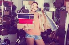 Retrato del adolescente que se coloca con los bolsos en tienda con los bolsos Foto de archivo libre de regalías