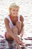 Retrato del adolescente que se sienta en la playa Fotos de archivo