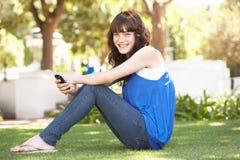 Retrato del adolescente que se sienta en parque Fotografía de archivo libre de regalías