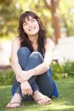 Retrato del adolescente que se sienta en parque Imagen de archivo libre de regalías