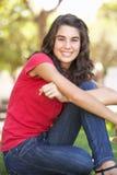Retrato del adolescente que se sienta en parque Foto de archivo libre de regalías
