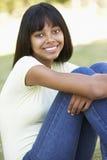 Retrato del adolescente que se sienta en parque Imagenes de archivo