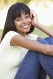 Retrato del adolescente que se sienta en parque Imagen de archivo
