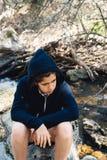 Retrato del adolescente que se sienta en roca cerca del río Foto de archivo libre de regalías