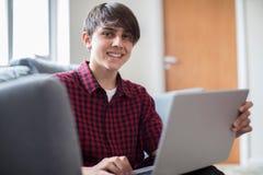 Retrato del adolescente que trabaja en el ordenador portátil en casa Imagen de archivo libre de regalías