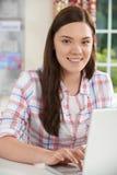 Retrato del adolescente que usa el ordenador portátil en casa Foto de archivo libre de regalías