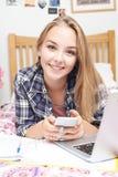 Retrato del adolescente que usa el teléfono móvil mientras que hace Homewor Imagenes de archivo