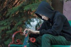 Retrato del adolescente relajante que mira el monopatín en sus manos Imágenes de archivo libres de regalías