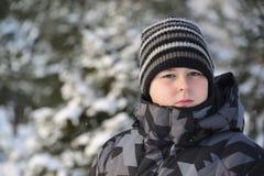 Retrato del adolescente serio en un bosque del pino en invierno Fotografía de archivo