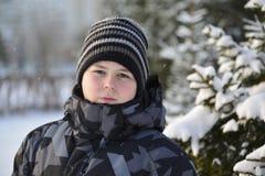 Retrato del adolescente serio en un bosque del pino en invierno Foto de archivo