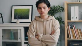 Retrato del adolescente serio que mira la cámara con la cara seria en casa almacen de metraje de vídeo