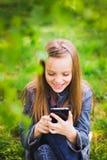 Retrato del adolescente sonriente con el teléfono móvil Imágenes de archivo libres de regalías