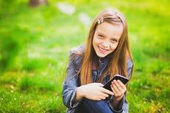 Retrato del adolescente sonriente con el teléfono móvil Fotos de archivo libres de regalías