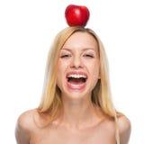 Retrato del adolescente sonriente con la manzana en la cabeza Imagen de archivo libre de regalías