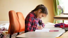 Retrato del adolescente sonriente con los auriculares que escribe ejercicio en cuaderno Foto de archivo libre de regalías