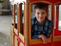 Retrato del adolescente sonriente en el tren de carromatos de madera Fotografía de archivo