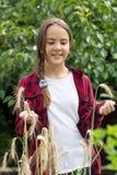 Retrato del adolescente sonriente en la camisa a cuadros roja que presenta con trigo maduro en campo Fotografía de archivo libre de regalías