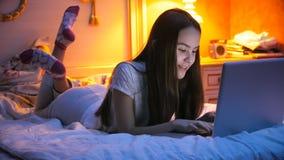 Retrato del adolescente sonriente que miente en cama y que charla en Internet Fotos de archivo