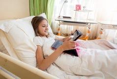 Retrato del adolescente sonriente que miente en cama y Internet de la ojeada en la tableta digital Fotografía de archivo libre de regalías