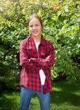 Retrato del adolescente sonriente que presenta en jardín con los manzanos Imagen de archivo