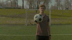 Retrato del adolescente sonriente que sostiene el balón de fútbol almacen de metraje de vídeo
