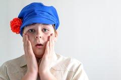 Retrato del adolescente sorprendido del muchacho en el casquillo nacional ruso con los clavos Fotografía de archivo libre de regalías