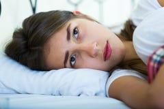 Retrato del adolescente triste en la cama casera Foto de archivo