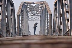 Retrato del adolescente triste en la depresión que se sienta en el puente en Imagen de archivo