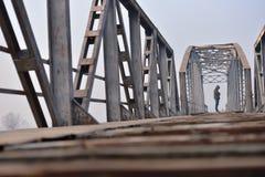 Retrato del adolescente triste en la depresión que se sienta en el puente en Fotografía de archivo