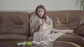 Retrato del adolescente triste envuelto en una sentada combinada en el sofá de cuero en casa en el fondo de las píldoras que mien almacen de video