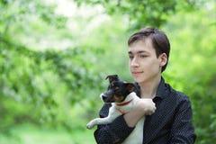 Retrato del adolescente y del perro felices hermosos Jack Russell Foto de archivo