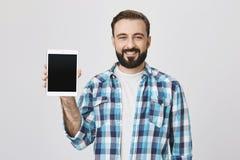 Retrato del adulto barbudo lindo en camisa comprobada casual, sosteniendo la tableta en mano derecha mientras que sonríe ampliame Imagenes de archivo