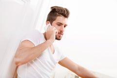 Retrato del adulto joven usando el teléfono Foto de archivo libre de regalías