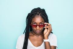 Retrato del africano joven emocionado femenino en gafas de sol en fondo azul foto de archivo