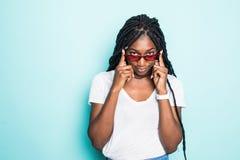 Retrato del africano joven emocionado femenino en gafas de sol en fondo azul imagenes de archivo